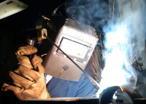 040604-N-7408M-001 Atlantic Ocean (June 4, 2004)-- Hull Technician 2nd Class Chris B. Millones of Sacramento, Calif. welds a piece of steel pipe in the pipe fitter's shop. Enterprise is currently underway in support of Summer Pulse 2004. Official U.S. Navy photo by Photographer's Mate Airman Justin McGarry. Image released by LT K. R. Stephens, PAO, CVN 65.